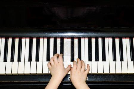 Photo pour De fille mains et piano clavier en gros plan, le concept de l'éducation - image libre de droit