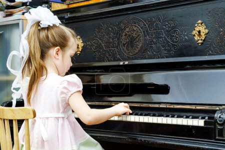 Cute little girl playing old piano