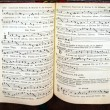 Vintage psalm book with chorus singing notes close...