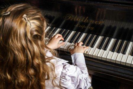 Photo pour Petite fille mignonne jouant le piano à queue dans l'école de musique, concept d'enfance - image libre de droit
