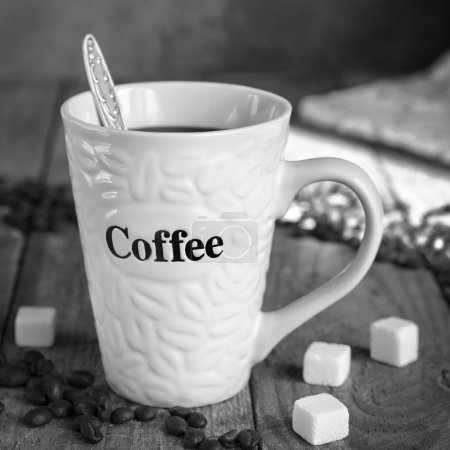 Mug of coffee on the old boards, black-and-white image