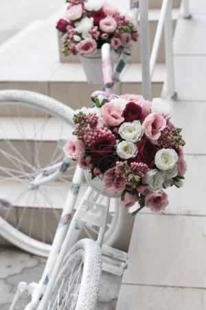 Photo pour Bouquet créatif de fleurs artificielles colorées sur vieux vélo blanc, rétro. Mise au point sélective et espace dans la zone brouillant les compositions pour la production de publicité et de texte . - image libre de droit