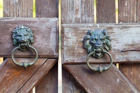 Vintage metal wrought iron door handle on an old wooden door