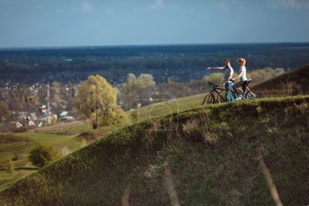 Photo pour Beau jeune couple amoureux à vélo sur la promenade viennent des montagnes - image libre de droit