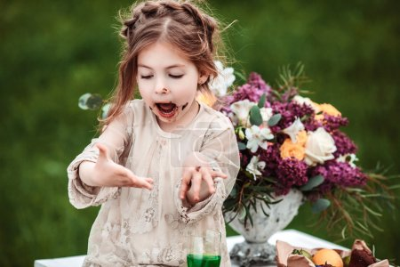 Photo for Little baby girl eats chocolate cake in nature at a picnic. The concept of a happy childhood - Royalty Free Image