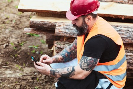 Worker in overalls and with a tattoo