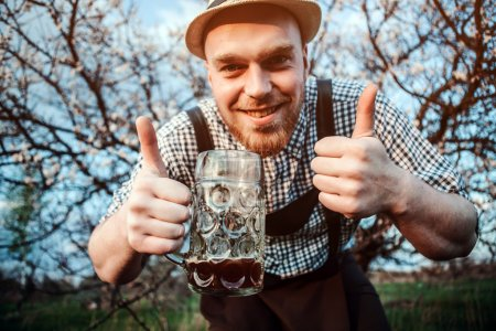 Photo for Happy smiling man with fresh brewed beer on the background of a blooming garden looking at the camera and shows that all is well. The theme is Oktoberfest, a guy in Bavarian style - Royalty Free Image