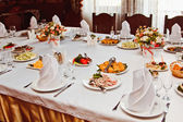 Elegantní krásné zdobené tabulka s jídla a nádobí na svatební recepce detail