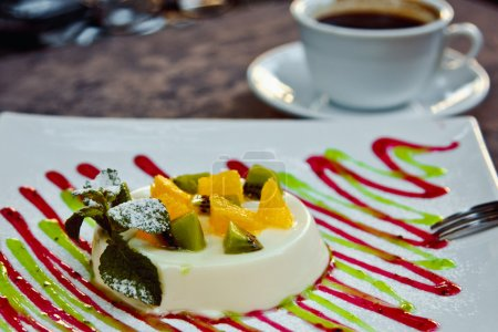 photo of italian panna cotta dessert with slices of kiwi, orange and mint leaf