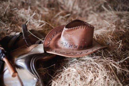 Photo pour Chapeau blanc de paille blanc de cowboy de rodéo de l'ouest américain avec la corde occidentale traditionnelle d'élevage sur une balle de foin dans une vieille grange de ranch en bois allumée par la lumière diffuse - image libre de droit
