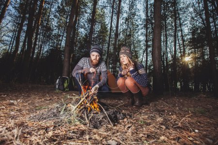 Photo for Couple of hikers starting a fire in the wood - Royalty Free Image
