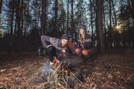 Photo pour Quelques randonneurs assis près du feu à la tente dans le bois - image libre de droit
