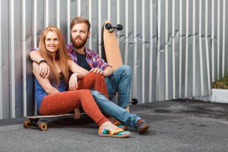 Young couple are holding skateboard outside