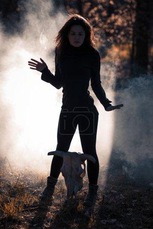 Photo pour Jeune sorcière avec crâne dans la forêt nocturne - image libre de droit