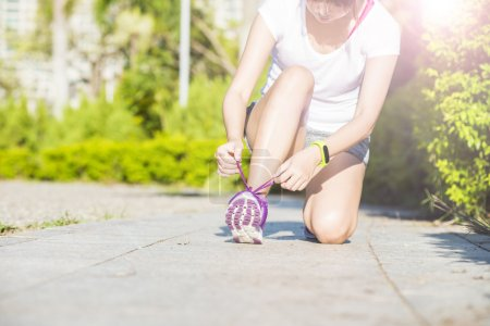 oung woman in fitness wear tying shoelaces outdoors
