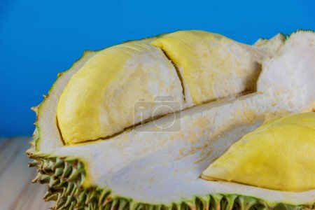 Image of ripe durian with yellow pulp on wood tabl...