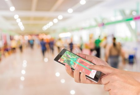 Photo for Male hand is holding a modern touch screen phone and Blurred image of people walking at shopping mall , blur background with bokeh - Royalty Free Image