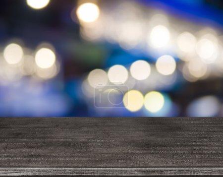 Photo pour Table en bois devant un fond abstrait de lampadaires flous - image libre de droit