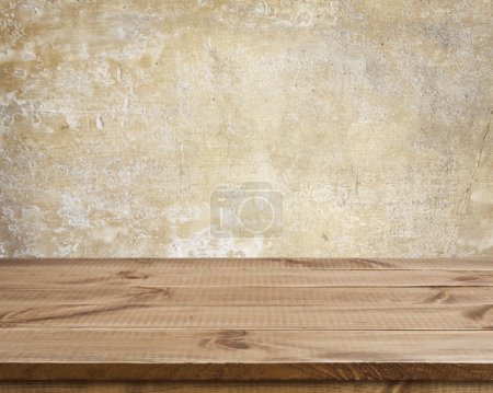 Wooden texture table surface over defocused ancient grunge wall background