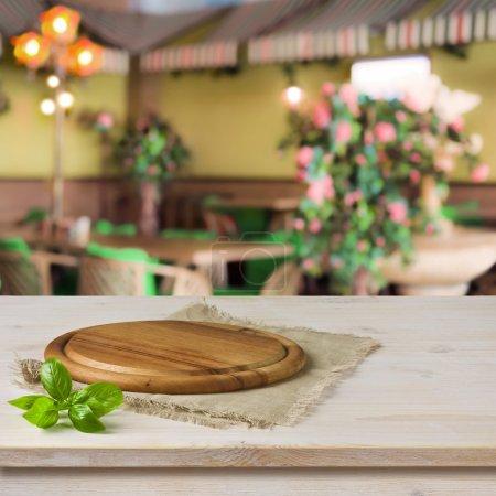 Foto de Tablero redondo en la mesa de la cocina sobre fondo interior café - Imagen libre de derechos