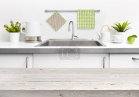 Photo pour Table en bois sur le fond intérieur de cuisine évier - image libre de droit