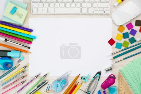 Various school supplies background with white sheet in the middle