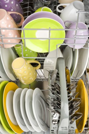 Background of clean dishes in dishwashing machine, front view