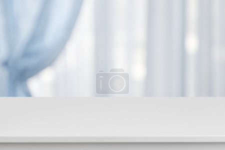 White table on defocuced window with blue curtain ...