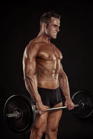 Bodybuilder guy doing exercises with big dumbbell