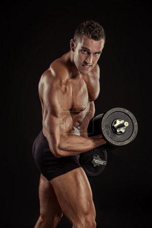 Bodybuilder guy doing exercises with dumbbells