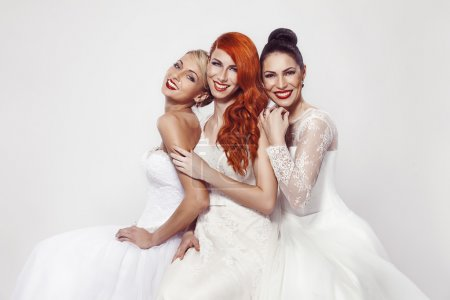 Photo for Portrait of a three beautiful woman in wedding dress isolated over white background - Royalty Free Image