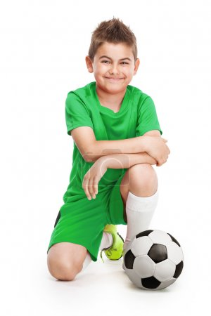 kneeling young soccer player with football