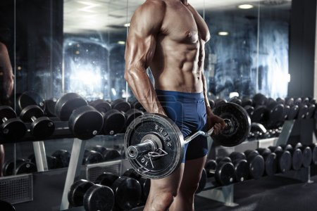 Photo for Muscular bodybuilder guy doing exercises with barbells in gym - Royalty Free Image