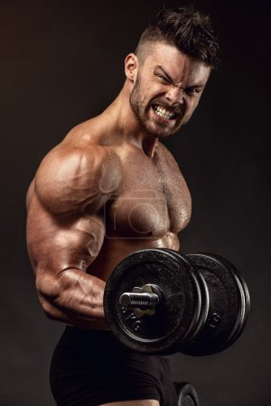 Muscular bodybuilder guy doing exercises with big dumbbells