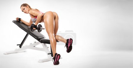 Nice sexy woman on a bench doing workout with dumbbell
