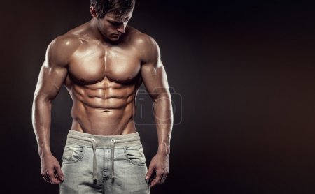 Photo for Strong Athletic Man Fitness Model Torso showing six pack abs. isolated on black background with copyspace - Royalty Free Image