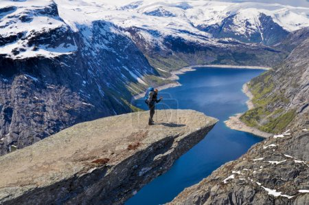 Photo for Hiker with backpack on Trolltunga rock high above scenic fjord in Norway - Royalty Free Image