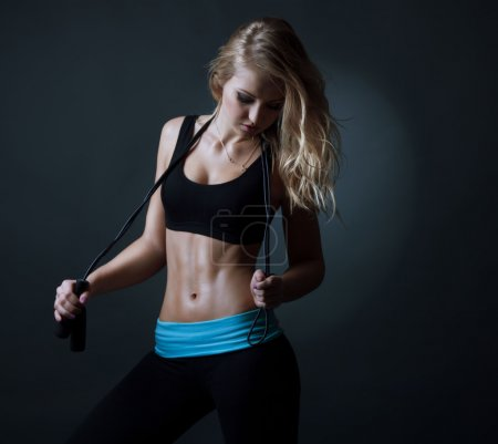 Sport  blond beautiful woman with skipping rope showing her well