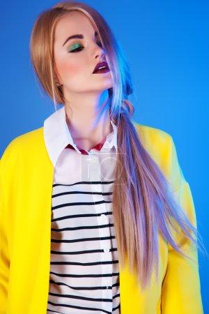 Foto de Moda portrain de mujer rubia en chaqueta amarilla de moda sobre fondo azul. - Imagen libre de derechos