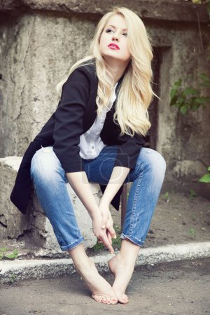 Sexy  blond woman in trendy jeans, white shirt and black jacket