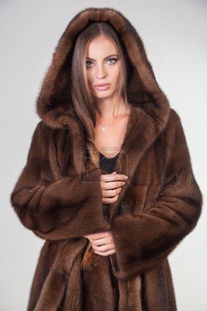Photo pour Belle femme qui pose en manteau de fourrure de la mode. modèle fille hiver en vêtements de luxe et neigeux capuche fourrure isolé sur fond gris. - image libre de droit