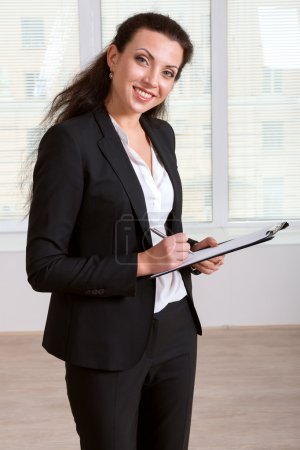 Girl in business suit writing in a document folder