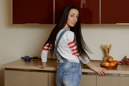 Housewife brunette in the home stands near the kitchen cupboard
