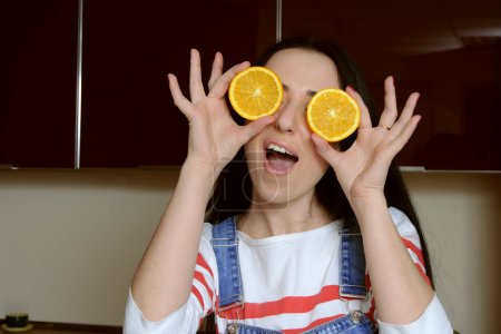 Housewife holding orange slices in front of her eyes and plays t
