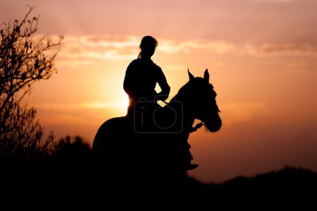 Silhouette of a girl riding a horse