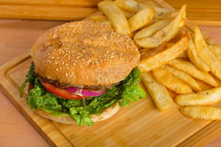 Tasty burger with melted cheese and thick succulent ground beef patty, lettuce, tomato, onion, sesame bun standing on wooden table
