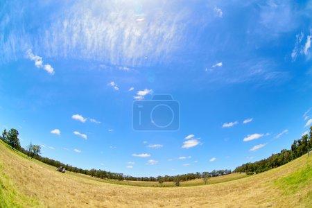 Australian rural field landscape with haystacks and blue sky. Fish eye lense