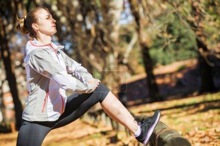 Photo pour Jeune femme sportive étirant et chauffant sur le banc avant de faire de l'exercice dans le parc d'automne - image libre de droit