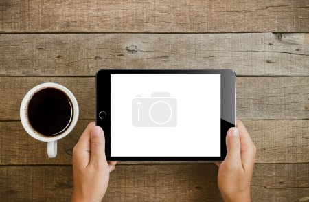 Photo for Hand holding tablet on wood table - Royalty Free Image