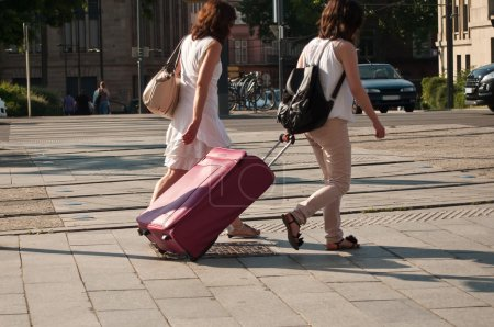Women with suitcase walking  in the street...